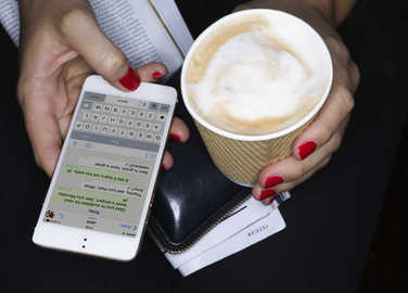 woman-texting-and-holding-coffee