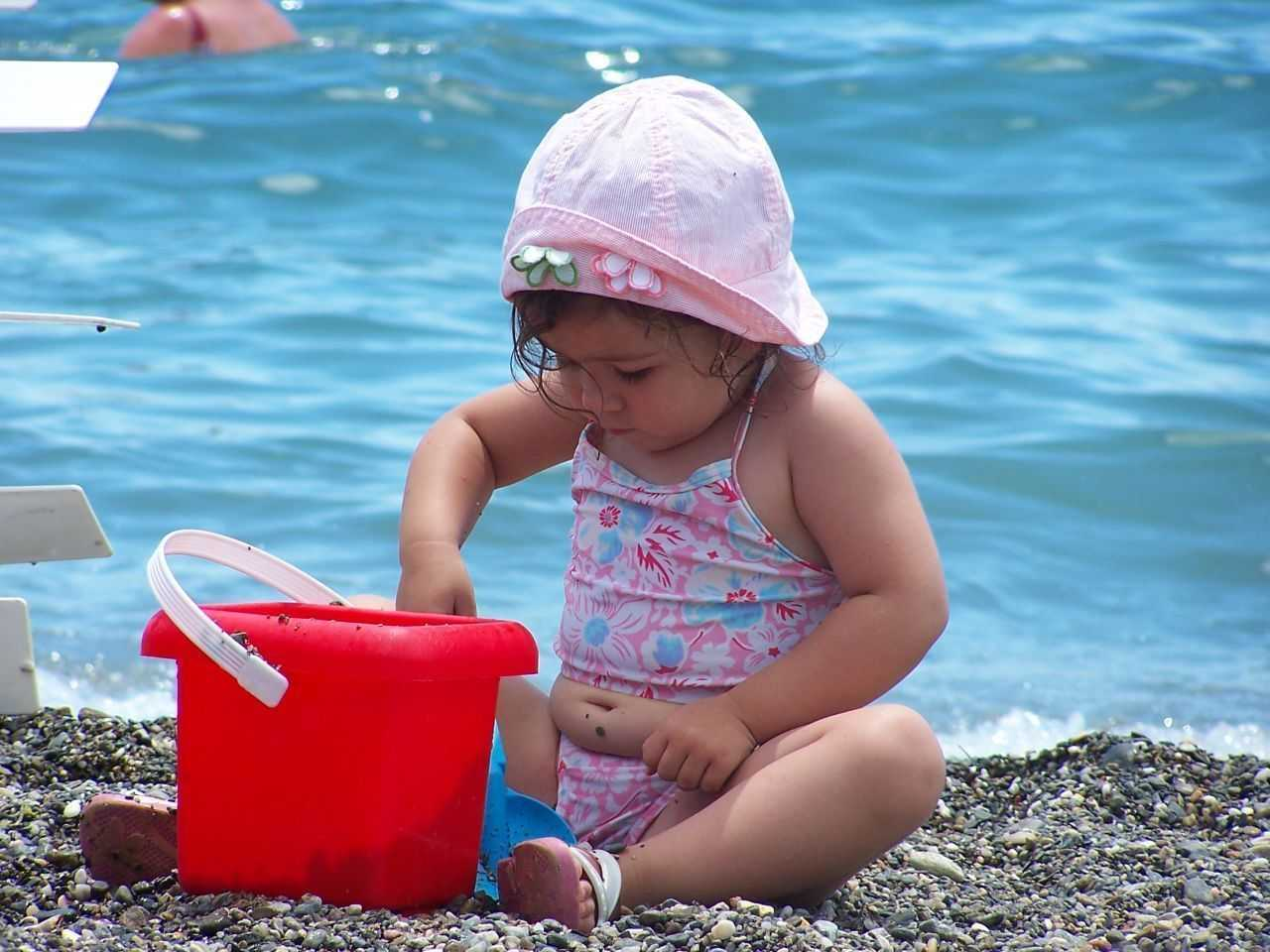 CREDIT: Small girl on a beach with a red bucket and blue spade