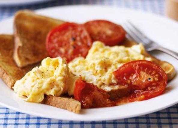 Scrambled eggs on toast with oven-baked tomatoes