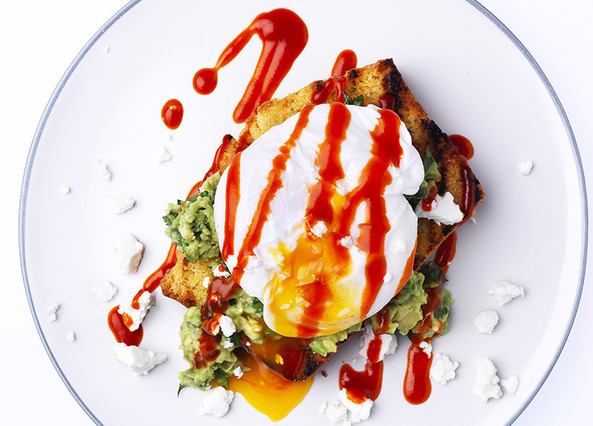Image: Eggs benedict on cornbread with guacamole, feta and sriracha