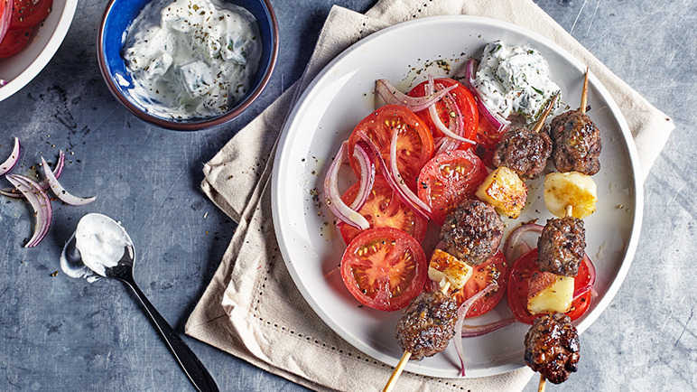 Image: Minted lamb kofta and halloumi skewers with tomato and red onion salad and minted cucumber yoghurt