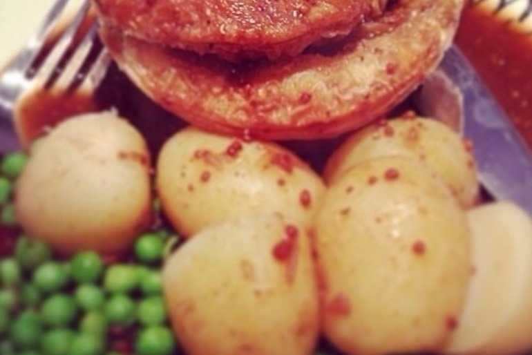 Steak pie, potatoes and peas all covered in gravy image