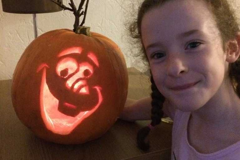 My daughter Brooke with our Olaf pumpkin!  image